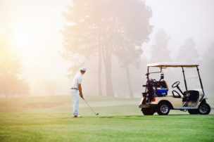 Person golfing with golf cart in picture