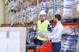 Workers With Tablet PC and Forklift in Warehouse