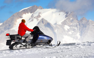 man on snowmobile with mountainous background