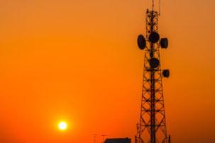 Telecommunication tower structure with sunset sky in silhouette background