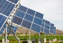 low angle of solar panels in field with mountains in the background