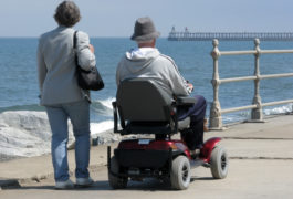 Elderly man riding motorized wheelchair with woman on seaside promenade.