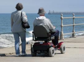 Elderly man riding motorized wheelchair with woman on seaside promenade.
